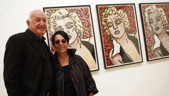 "Don and Mera Rubell at their collection in front Keith Haring's ""Marilyn"" Paintings."